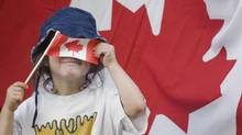 A young girl hides behind a small Canadian flag during the annual Canada Day parade in Montreal, Sunday, July 1, 2012. (Graham Hughes/THE CANADIAN PRESS)