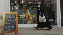 "A woman walks past an advertising board on which ""Je Suis Charlie!"" is written outside a cafe in Brick Lane, east London January 14, 2015. (LUKE MACGREGOR/REUTERS)"
