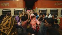Women try to enter the ladies' compartment of a crowded train heading toward Delhi at Noli Railway Station in Utter Pradesh in this Nov. 10, 2012 file photo. A railway fare hike and increase in diesel fuel prices this week are among Prime Minister Manmohan Singh's economic reforms. (NAVESH CHITRAKAR/REUTERS)