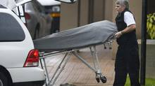 The second of six bodies are removed on Oct. 20, 2007, from the apartment tower where six men were found dead in Surrey, B.C. (Jeff Vinnick for The Globe and Mail)