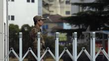 A Chinese People's Liberation Army soldier stands guard in front of 'Unit 61398', a secretive Chinese military unit, in the outskirts of Shanghai, February 19, 2013. The unit is believed to be behind a series of hacking attacks, a U.S. computer security company said. (Carlos Barria/Reuters)