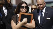 A woman carrying a photo is escorted from where the family of movie-theatre shooting victim Micayla Medek had gathered before Ms. Medek's funeral in Denver on Thursday. (Ted S. Warren/Associated Press)