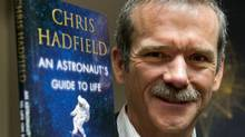 "Retired Canadian astronaut Chris Hadfield holds a copy of his new book ""an Astronaut's Guide to Life on Earth"" while on a media tour Wednesday, November 27, 2013 in Montreal. (Ryan Remiorz/THE CANADIAN PRESS)"