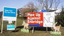 Competing campaign signs are seen in Kitimat, B.C. on Saturday, April 12, 2014, as voters cast their ballots in the town's plebiscite on the Northern Gateway pipeline project. (Robin Rowland/THE CANADIAN PRESS)