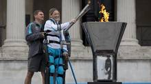 Claire Lomas, who was paralysed in a horse riding accident five years ago, stands on robotic legs to light the Paralympic cauldron at Trafalgar Square in London, August 24, 2012. (NEIL HALL/Reuters)