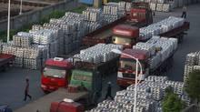Workers walk through an aluminium ingots depot in Wuxi, Jiangsu province Sept. 26, 2012. (ALY SONG/REUTERS)