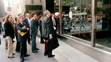 Somber-faced men stand outside the New York offices of a major mutual fund group watching an electronic display inside report the precipitous fall in the stock market on Oct. 19, 1987. (G. PAUL BURNETT/AP)