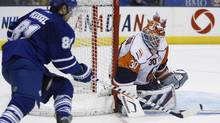 Toronto Maple Leafs forward Phil Kessel, left, tries for a wraparound past New York Islanders netminder Dwayne Roloson on Monday, Nov. 23, 2009 in Toronto. (NATHAN DENETTE)