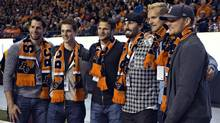 Members of the NHL Vancouver Canucks (L-R) wearing BC Lions scarves Ryan Kesler, Mason Raymond, Kevin Bieksa, Jason Garrison, Alexander Edler and Corey Schneider pose for a photo while attending the Lions' CFL football game against the Calgary Stampeders in Vancouver, British Columbia October 6, 2012. (ANDY CLARK/REUTERS)