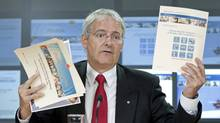 Liberal MP Marc Garneau holds up papers as he speaks about cuts to the census during a press conference in Ottawa, Wednesday July 14, 2010. (Adrian Wyld/THE CANADIAN PRESS)