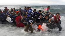 Refugees and migrants struggle to jump off an overcrowded dinghy on the Greek island of Lesbos on Oct. 2, after crossing in rough seas from Turkey. (DIMITRIS MICHALAKIS/REUTERS)
