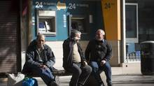 Men sit on a street bench near two unused 24-hour automated teller machines operated by Bank of Cyprus Plc in Nicosia, Cyprus. European policy makers weighed how far to push Cyprus after lawmakers in the Mediterranean nation rejected an unprecedented levy on bank deposits, throwing into limbo a rescue package designed to keep it in the euro. (Simon Dawson/Bloomberg)