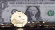 The Canadian dollar coin, the Loonie, is displayed next to the US dollar, January 30, 2015 in Montreal. (Paul Chiasson/The Canadian Press)