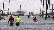 People wade and paddle down a flooded street as HurricaneSandyapproaches, Monday, Oct. 29, 2012, in Lindenhurst, N.Y. Gaining speed and power through the day, the storm knocked out electricity to more than 1 million people and figured to upend life for tens of millions more. (Jason DeCrow/AP Photo)