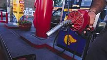 A man pumps gas at a Toronto gas station.