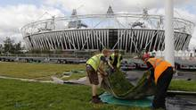 Workers prepare membrane covered with meadow flowers and turf outside the Olympic Stadium ahead of the Opening Ceremony in the London 2012 Olympic Park at Stratford in London July 13, 2012. (LUKE MACGREGOR/Reuters)