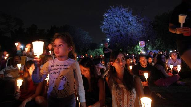 People hold candles as they gather outside the Galileo Galilei planetarium to observe Earth Hour in Buenos Aires, March 29. (Marcos Brindicci/Reuters)