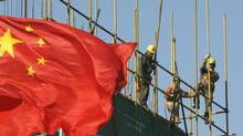 Workers install scaffolding at a construction site as a Chinese national flag flies near by in central Beijing, January 11, 2010. (REUTERS)
