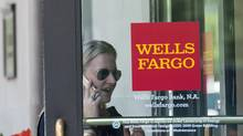 This file photo taken on May 27, 2016 shows a woman walking into a Wells Fargo bank in Washington, DC. (NICHOLAS KAMM/AFP/Getty Images)