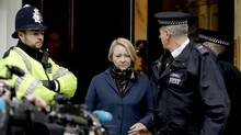 Swedish prosecutor Ingrid Isgren walks to a vehicle flanked by British police officers as she leaves the entrance of the Ecuadorian embassy in London, Monday, Nov. 14, 2016. Isgren arrived at the embassy Monday to question Wikileaks founder Julian Assange about allegations concerning possible sexual misconduct committed in Sweden six years ago. (Matt Dunham/AP)
