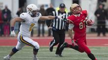 Laval Rouge et Or's Jonathan Breton-Robert runs away from Laurier Golden Hawks' Taylor Calverley during first quarter action at the Uteck Bowl for the CIS national semifinal Saturday, November 19, 2016 at Laval University in Quebec City. (Jacques Boissinot/THE CANADIAN PRESS)