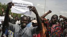 File photo from Oct. 18, 2012, showsa man carrying a sign reading 'No to the destructive soldiers of ECOWAS' as Malians opposed to a military intervention to retake Mali's Islamist-controlled north march in the streets of the capital, Bamako. (Harouna Traore/Associated Press)