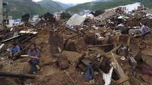 In this photo released by China's Xinhua News Agency, survivors rest on the ruins after a strong earthquake hit Ludian county, Zhaotong city, southwest China's Yunnan Province, Monday, Aug. 4, 2014. (Zhao Jiarong/Associated Press)