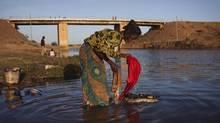 Oumi Sangare washes clothes in a river in Markala, Mali, where French troops are stationed, January 18, 2013. (JOE PENNEY/REUTERS)