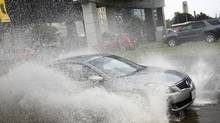 A car pass a flooded section of the Lakeshore Blvd. in downtown Toronto. (Fernando Morales/The Globe and Mail)