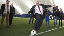 Toronto Mayor Rob Ford kicks a soccer ball toward a youth player in goal at Soccer World in Toronto on Wednesday, April 9, 2014. Mr. Ford was the guest at an announcement of a partnership between Soccerworld Polson Pier and the Real Madrid Foundation to expand soccer clinics across Ontario and Quebec. Soccerworld Director and Co-Founder, Robert Ortali, is at left in the scarf. (Peter Power for the Globe and Mail)