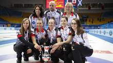 Canada's players foreground from left: Rachel Homan, Emma Miskew, Joanne Courtney, Lisa Weagle, Cheryl Kreviazuk and their team members pose with the winning trophy and medals after the CPT World Women's Curling Championship 2017 final match against Russia at the Capital Gymnasium in Beijing, on March 26, 2017. (Andy Wong/AP)