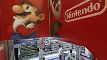 Shoppers walk under the logo of Nintendo and Super Mario characters at an electronics store in Tokyo on May 7, 2014. (SHIZUO KAMBAYASHI/THE ASSOCIATED PRESS)