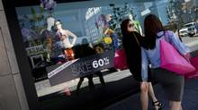 Shoppers outside the Holt Renfrew flagship store on Bloor Street in Toronto (Moe Doiron/The Globe and Mail)