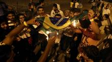 Lebanese soccer fan who support Germany burn a Brazilian flag after Brazil lost the game against Germany (Bilal Hussein/AP)