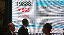 Pedestrians walk past an electronic sign showing the Hang Seng Index in the Central district of Hong Kong on January 11, 2016. Hong Kong stocks began the week sharply lower, slipping 2.8 per cent, or 565.21 points, to close at 19,888.50 as bourses in mainland China plummeted again. (ISAAC LAWRENCE/AFP/Getty Images)