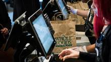 Employees ring up customers at the checkout counter of a Whole Foods location in New York. (Mark Kauzlarich/Bloomberg)
