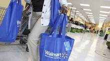 A shopper carries her purchases from a newly opened Walmart Neighborhood Market in Chicago, in this September 21, 2011 file photo. (JIM YOUNG/REUTERS)