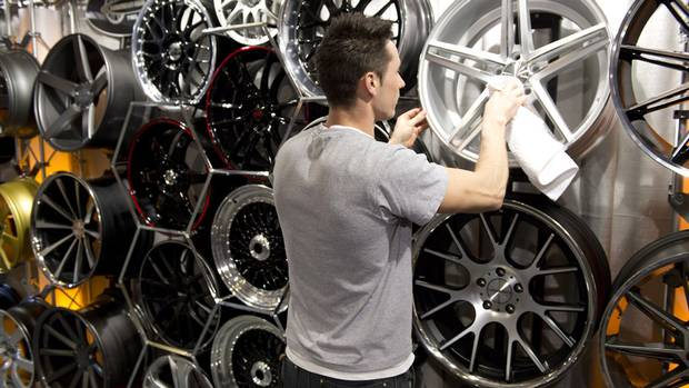 A man polishes car wheels at the Canadian International Auto Show in Toronto on February 14, 2013. (Frank Gunn/CP Photo)