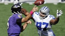 Baltimore Ravens quarterback Joe Flacco, left, throws to a receiver as he is pressured by Dallas Cowboys defensive end Jason Hatcher in the first half of an NFL football game in Baltimore, Sunday, Oct. 14, 2012. (Nick Wass/AP)