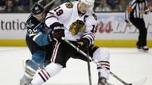 Chicago Blackhawks center Jonathan Toews controls the puck in front of San Jose Sharks defenceman Dan Boyle (Marcio Jose Sanchez/AP)