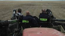 RCMP officers, shown in this police handout photo, stand in the bucket of a tractor as they chase down car-theft suspects across a muddy field in Briercrest, Sask., on Friday May 2, 2014. (RCMP-HO/THE CANADIAN PRESS)