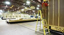Construction tradesmen build portable housing for oil sands workers at the ATCO Structures facility in Calgary earlier this year. (Jeff McIntosh For The Globe and Mail)