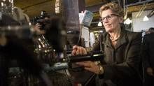 Premier Kathleen Wynne brews a cup of coffee in a Toronto coffee shop on Thursday January 30, 2014. The premier announced Ontario's minimum wage will be increased to $11 an hour effective June 1, up 75 cents. (Chris Young/The Canadian Press)