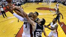 Miami Heat guard Dwyane Wade, left, drives to the basket against San Antonio Spurs guard Manu Ginobili and forward Tim Duncan during Game 4 of the NBA finals at American Airlines Arena in Miami on Thursday. (Larry W. Smith/USA Today Sports)