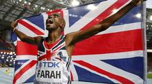 Mo Farah of Britain holds his national flag as he celebrates winning the men's 5,000 metres final during the IAAF World Athletics Championships at the Luzhniki stadium in Moscow August 16, 2013. (DOMINIC EBENBICHLER/REUTERS)