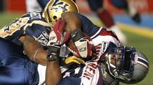Winnipeg Blue Bombers RB Chris Garrett grabs Montreal Alouettes DT Jermaine McElveen after a late second quarter interception by the Alouettes during CFL action in Winnipeg on Friday, Sept. 30, 2011. THE CANADAIN PRESS/Jason Halstead (Jason Halstead/CP)