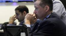 Neil Catania, right, works with fellow traders on the floor of the New York Stock Exchange Thursday, Aug. 15, 2013. Warnings of weaker sales from two major companies and concern that the Federal Reserve could ease off its support for the economy sent the stock market spiraling lower Thursday. (Richard Drew/AP)