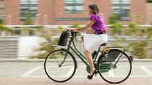 Young Gen Y woman, biking through town to work. (thinkstock.com)