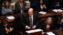 B.C. Finance Minister Mike de Jong tables the budget in the Legislative Assembly in Victoria on Feb. 17, 2015, as Premier Christy Clark, left, applauds. (Chad Hipolito/The Canadian Press)