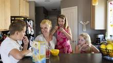 Ceone Fournier, centre, and her kids Owen, 11, left to right, Maisy, 6, and Claire, 9, have a snack in their home in Spruce Grove, Alta., on July 24. Fournier was involved in the Health Canada consultations on the proposed labeling modernization. (AMBER BRACKEN/The Globe and Mail)